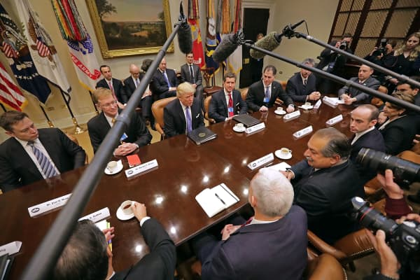 President Donald Trump (C) leads a meeting with invited business leaders and members of his staff in the Roosevelt Room at the White House January 23, 2017 in Washington, DC. Business leaders included Elon Musk of SpaceX, Wendell Weeks of Corning, Mark Sutton of International Paper, Andrew Liveris of Dow Chemical, Alex Gorsky of Johnston & Johnson and others.