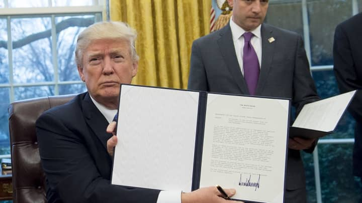 US President Donald Trump holds up an executive order withdrawing the US from the Trans-Pacific Partnership after signing it alongside White House Chief of Staff Reince Priebus (R) in the Oval Office of the White House in Washington, DC, January 23, 2017.