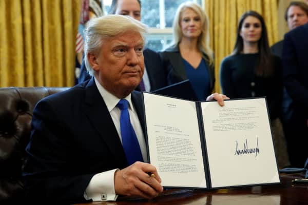 President Donald Trump holds up a signed executive order to advance construction of the Keystone XL pipeline at the White House in Washington January 24, 2017.