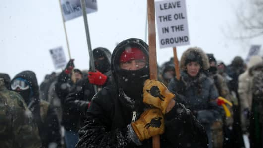 """A Native American man leads a protest march with veterans and activists outside the Oceti Sakowin camp where """"water protectors"""" continue to demonstrate against plans to pass the Dakota Access pipeline adjacent to the Standing Rock Indian Reservation, near Cannon Ball, North Dakota, U.S., December 5, 2016."""