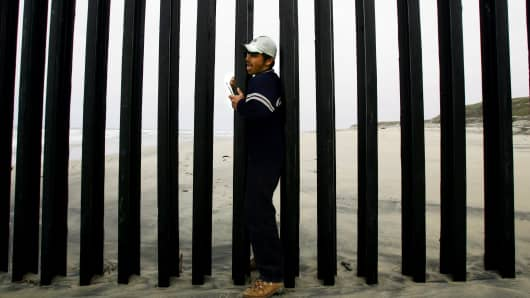 A man from Mexico crosses the wall border between Mexico and Unites States at the beach of Tijuana, Mexico.