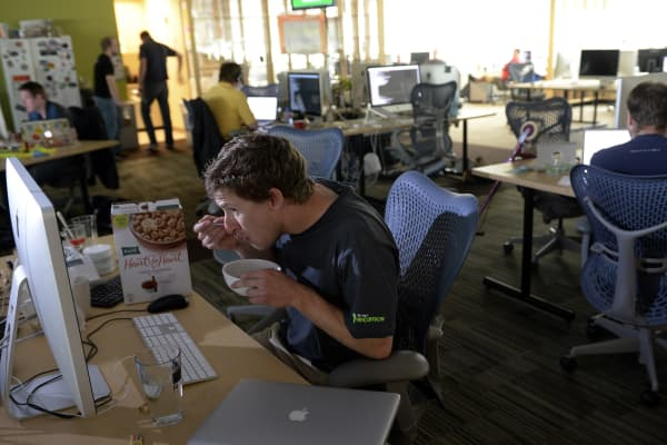 Twenty-seven-year-old Garston Tremblay, a developer, enjoys a bowl of cereal at his desk while at work at Rally Software Development.