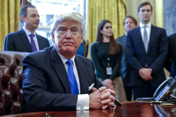 U.S. President Donald Trump sits after signing one of five executive orders on Jan. 24, 2017.