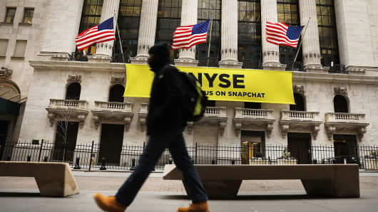 People walk in front of the New York Stock Exchange.