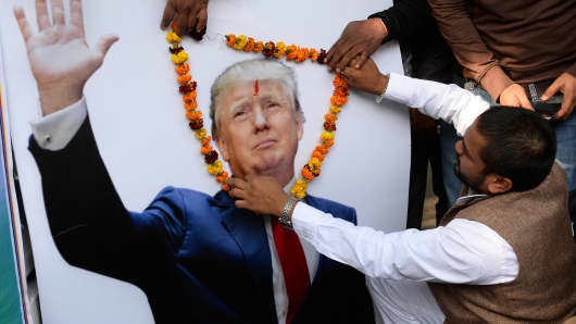 Hindu Sena party president, Vishnu Gupta places a garland of flowers on a poster of US President-elect Donald Trump during an event in New Delhi on January 19, 2017.