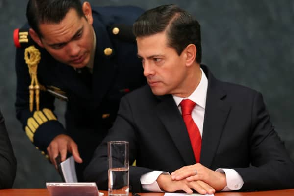 Mexico's President Enrique Pena Nieto speaks with an assistant during the deliver of a message about foreign affairs at Los Pinos presidential residence in Mexico City, Mexico, January 23, 2017.