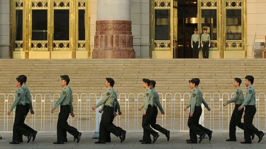 Chinese military policemen march past the Great Hall of the People beside Tiananmen Square in Beijing.