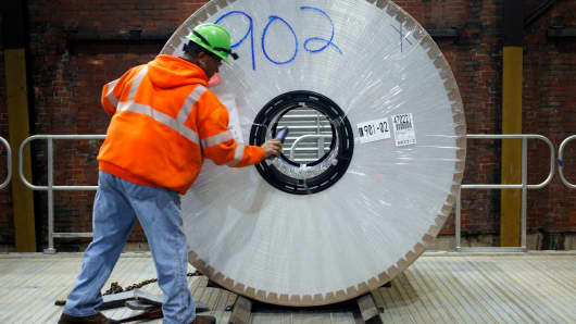 A worker loads an aluminum coil onto a loading dock at the Arconic manufacturing facility in Alcoa, Tennessee.