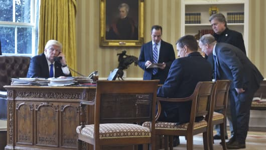 President Donald Trump speaks on the phone with Russia's President Vladimir Putin from the Oval Office of the White House on January 28, 2017.  Looking on from second left: White House Chief of Staff Reince Priebus, National Security Advisor Michael Flynn, White House Press Security Sean Spicer, and Counselor to the President Stephen Bannon.