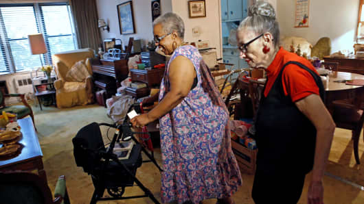 Carolyn Allen, left, a 69-year-old widow who has suffered two strokes, makes her way to the living room with roommate Marcia Rosenfeld, who owns the apartment Allen lives in New York, July 17, 2014. The two women are roommates thanks to a home-sharing program run by a New York-based nonprofit agency.