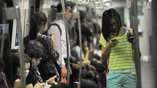 People use their phones while taking the Mass Rapid Transit (MRT) train in Singapore.