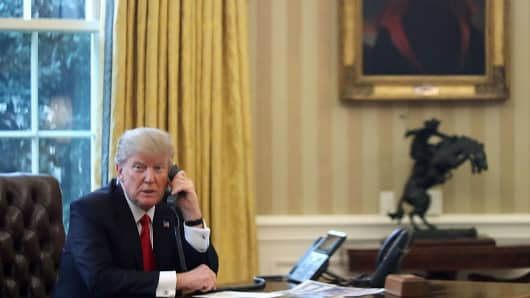 President Donald Trump is seen through a window speaking on the phone on Jan. 29, 2017.