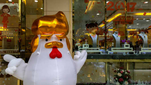 Uncertainty over U.S. President Donald Trump's term in office will boost gold prices, an Australian asset manager says. In this photo taken on January 31 in the China,  an inflatable rooster figure with a Donald Trump hairstyle and hand gestures, stands outside a gold shop to attract customers.