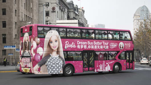 A double decker bus featuring an advertisement for Mattel's Barbie product turns onto the Bund in Shanghai, China, on Wednesday, Jan. 4, 2017.