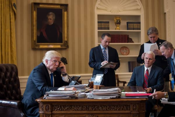 President Donald Trump speaks on the phone with Russian President Vladimir Putin in the Oval Office of the White House, January 28, 2017 in Washington, DC.