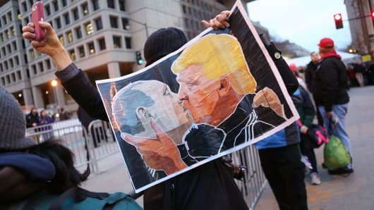 A protester holds a poster depicting President-elect Donald Trump and Russian President Vladimir Putin kissing during an anti-Trump demonstration on January 20, 2017 in Washington, DC.