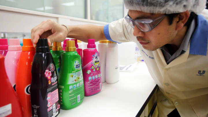 A Unilever NV employee inspects bottles of Comfort and Breeze brand household cleaning products in the detergents laboratory at the company's Research and Development Center in Lat Krabang near Bangkok, Thailand, Oct. 16, 2012.