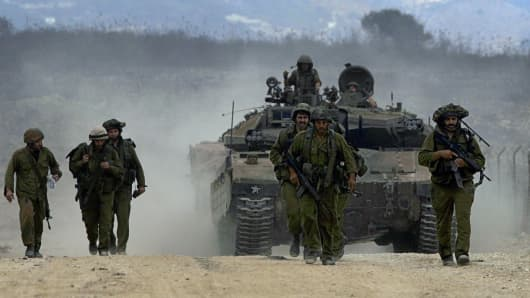 Israeli soldiers march in front a Merkava tank