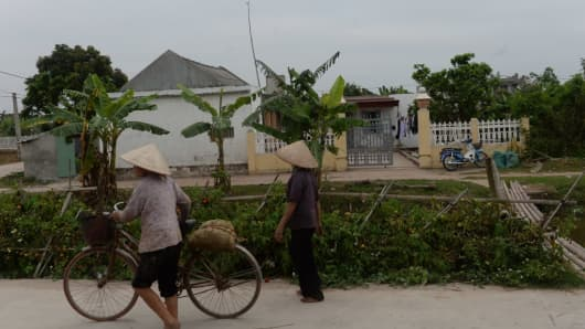 Villagers walk past the native home of Doan Thi Huong, a suspect involved in the assassination of Kim Jong-Un's half-brother, in Nghia Hung district, northern province of Nam Dinh on February 22, 2017.