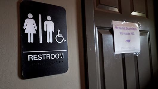 "A unisex sign and a 'We do not discriminate"" slogan outside a bathroom in Durham, North Carolina."