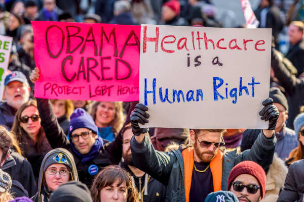 Demonstrators hold banners to protest Republican plans to repeal the Affordable Care Act, in Los Angeles.