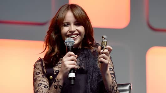 Felicity Jones on stage holding a Jyn Erso figurine during the Rogue One Panel at the Star Wars Celebration.