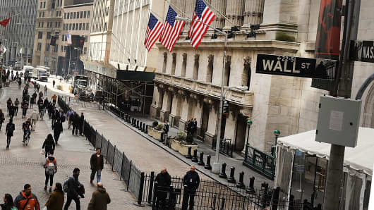 Pedestrians walk by the New York Stock Exchange in New York.