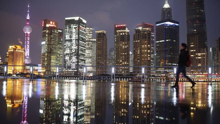 A woman walks at the Bund in front of the financial district of Pudong in Shanghai, China.