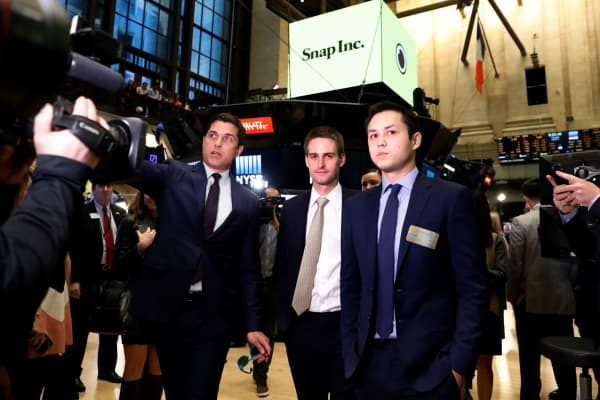 Snap co-founders Evan Spiegel and Bobby Murphy walk on the floor before the opening bell of the New York Stock Exchange with NYSE Group President Thomas Farley shortly before the company's IPO in New York, March 2, 2017.