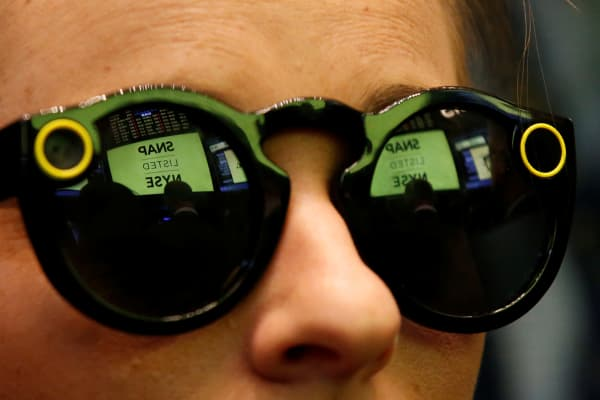 A woman wears Snapchat Spectacles on the floor of the New York Stock Exchange (NYSE) while waiting for Snap Inc. to list their IPO in New York, U.S., March 2, 2017.