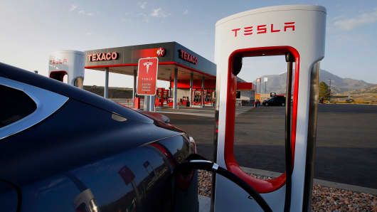 A Tesla Motors vehicle sits plugged in at a charging station near a Texaco gas station in Nephi, Utah.