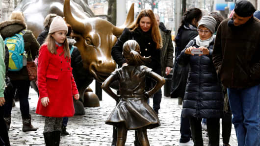 People look at a statue of a girl facing the Wall St. Bull in the financial district of New York, March 7, 2017.