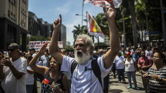 Demonstrators shouts slogans during a protest against austerity measures in front of the Legislative Palace in Rio de Janeiro, Brazil, on Monday, Dec. 12, 2016.