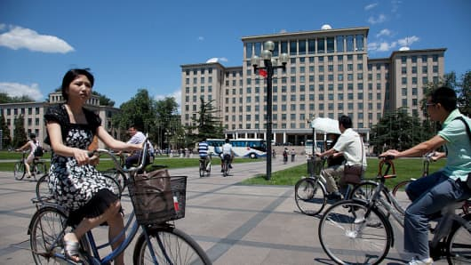 Students cycle past the central main building on campus at Tsinghua University in Beijing, China.