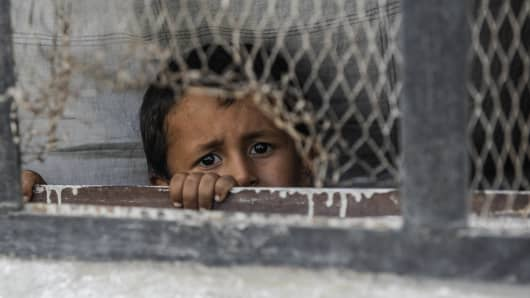 A boy looks out from a window of his home in the border town of Jarablus, Syria.