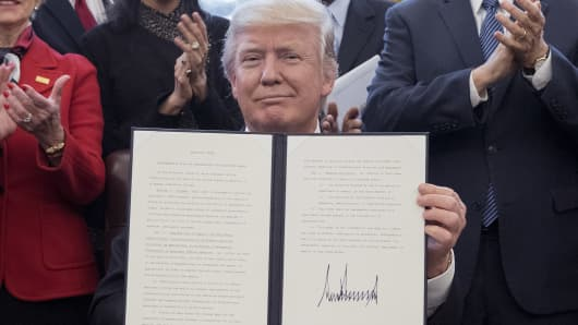 President Donald Trump holds up a signed executive order entitled 'Comprehensive Plan for Reorganizing the Executive Branch' in the Oval Office of the White House in Washington, D.C., U.S., on Monday, March 13, 2017.