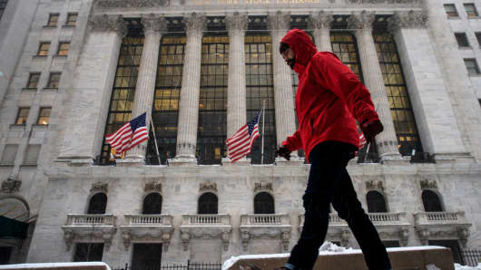 A pedestrian walks past the New York Stock Exchange.