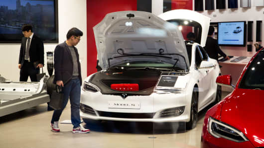 Customers look at a Tesla Model S 90D electric vehicle at the company's showroom in Hanam, South Korea.