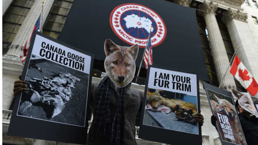 Wearing coyote masks and business suits and waving signs against Canada Goose and their use of fur, PETA members gather outside the New York Stock Exchange on March 16, 2017 to protest as Canada Goose makes its initial public offering in New York.