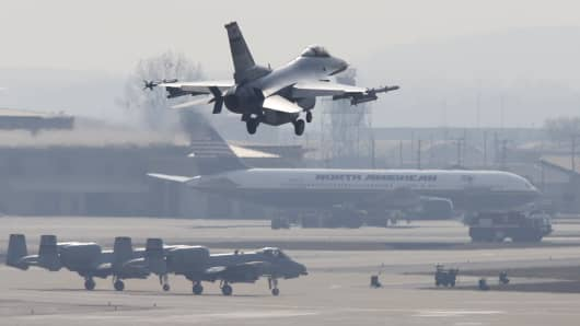 A F-16 fighter jet (top) belonging to the U.S. Air Force comes in for a landing at a U.S. air force base in Osan, south of Seoul.