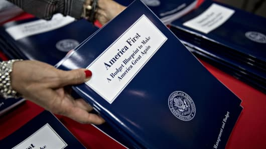 "An employee arranges copies of President Donald Trump's fiscal 2018 budget request, ""America First: A Budget Blueprint to Make America Great Again,"" at the Government Printing Office library in Washington on Thursday, March 16, 2017."