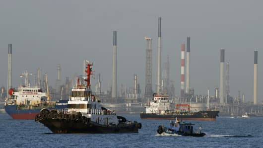 Vessels pass an oil refinery in the waters off the southern coast of Singapore.