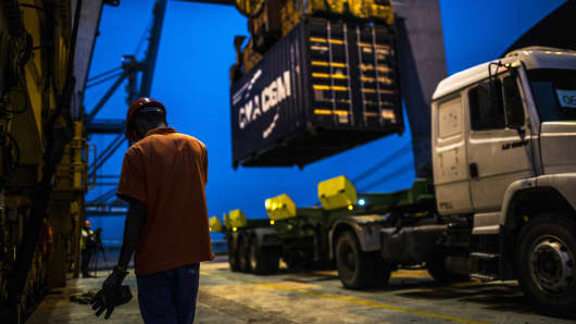 A worker waits as a shipping container is unloaded from the Hapag-Lloyd Holding AG Prague Express cargo ship onto a truck in Rio de Janeiro, Brazil.
