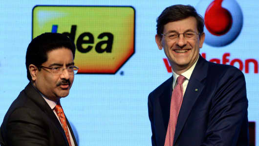Vodafone Group CEO Vittorio Colao (R) shakes hand with chairman of India's Aditya Birla Group Kumar Mangalam Birla during a news conference in Mumbai on March 20, 2017.