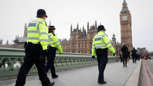 Police patrol across Westminster Bridge toward the Houses of Parliament in central London on March 23, 2017 after the bridge reopened to traffic following its closure during the March 22 terror attack.