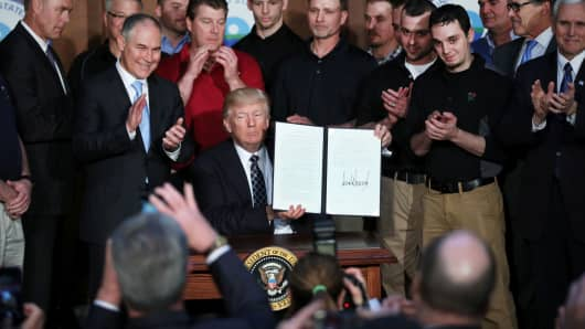 President Donald Trump holds up an executive order on