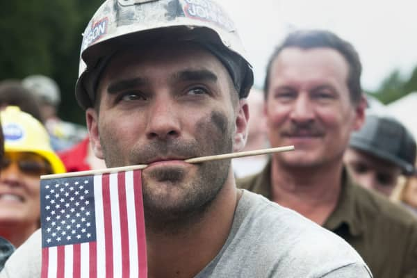 A coal miner in Ohio holds an American flag.