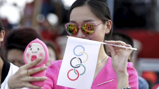 A local woman takes a selfie with an Olympics flag as she waits for IOC's announcement of the winner city for the 2022 winter Olympics bid