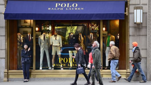 Shoppers walk past the entrance to the Polo Ralph Lauren clothing store on Fifth Avenue in Midtown Manhattan in New York City.