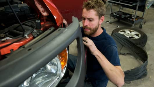 An auto repair worker takes apart the front of a car as he works to repair body damage at Admiration Auto Body in Aurora, Colorado.